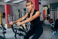 exersizing的自行车的白肤金发的妇女 免版税库存图片