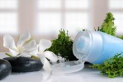 Exfoliating gel with seaweed in a bath. Blue exfoliating gel with seaweed on a white glass table in a bath Royalty Free Stock Photos