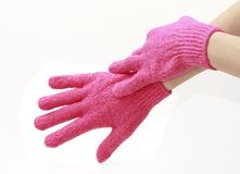 Exfoliating gloves isolated. Female hands in exfoliating pink gloves close up on white background Stock Images