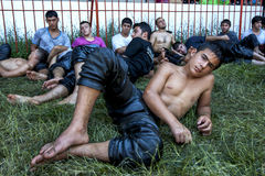 Exhasted wrestlers relax in the shade after competing at the Kirkpinar Turkish Oil Wrestling Festival in Edirne in Turkey. Stock Images