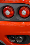 Exhaust and brake. Detail of exhaust pipes and tail lights on red car Stock Photo