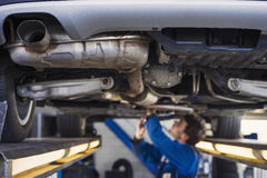 Exhaust of a car with mechanic underneath. Exhaust of a car on the bridge at a auto repair shop with a mechanic underneath stock photo