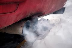 The exhaust gases of the car white thick smoke from the chimney in the winter against the white snow stock image