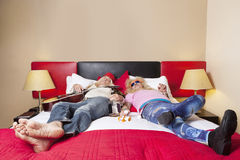 Exhaust male friends sleeping on bed Stock Photo