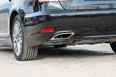 Exhaust pipe. Chrome exhaust pipe of black powerful sport car bumper Royalty Free Stock Photo
