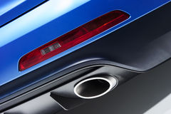 Exhaust pipe. Chrome exhaust pipe of blue powerful racing car bumper with red back lighting Stock Images