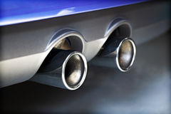 Exhaust pipe pollution. Chrome twin exhaust pipe blowing smoke fumes Royalty Free Stock Photos