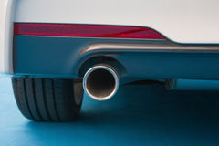 Exhaust pipe of a white car. On blue carpet Royalty Free Stock Photography