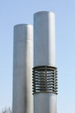 Exhaust pipes. Two silver-colored exhaust pipes with blue sky in the background Royalty Free Stock Photos