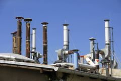Exhaust pipes. Numerous exhaust pipes on an old factory roof Stock Photography
