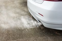 Exhaust smoke clouds from white car, air pollution concept.  Stock Photos