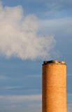 Exhaust tower. Brick exhaust tower with steam against blue sky Stock Photo