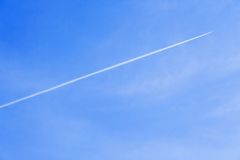 Exhaust trail seen behind a ai. Rcraft very high in the sky Stock Photo