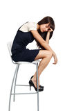 Exhausted. Young businesswoman sitting on a tall chair looking exhausted Stock Image