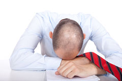 Exhausted. A business man putting his head on the desk Royalty Free Stock Photos