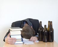 Exhausted. Businessman sleeping at the desk after too many beers Stock Photos