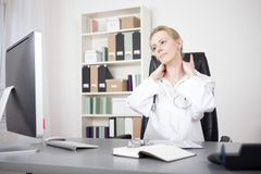 Exhausted Adult Woman Doctor Holding her Nape. Exhausted Adult Woman Doctor Sitting at her Table While Holding her Nape and Looking at the Computer Screen Royalty Free Stock Photography