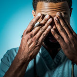 Exhausted African American Doctor Rubbing His Eyes. Studio shot of a young African American doctor suffering fatigue and rubbing his eyes Royalty Free Stock Image