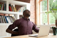 Exhausted african american male office worker having back discom. Young exhausted african american male office worker having back discomfort at work desk in Royalty Free Stock Photos