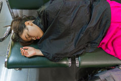 Exhausted Asian female sleeping at the airport. Exhausted Asian female sleeping in the airport royalty free stock photos
