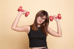 Exhausted Asian woman with dumbbells. On beige background stock photos