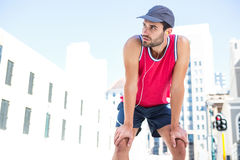 Exhausted athlete leaning forward after an effort Royalty Free Stock Photo
