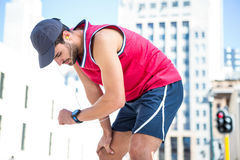 Exhausted athlete looking at his stopwatch Royalty Free Stock Photos
