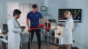 Exhausted athlete suddenly interrupt treadmill test because of feeling bad. Doctors at that time have recorded his EKG data. In Scientific Sports Laboratory stock footage