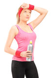 Exhausted athletic woman in sportswear holding a bottle of water Stock Photography