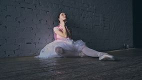 Exhausted ballerina sits on the floor and rests. Tired ballerina on the floor. theme of persistence stock video footage