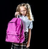 Exhausted beautiful little schoolgirl carrying a big schoolbag royalty free stock photography