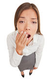 Exhausted or bored woman yawning. Exhausted or bored woman in yawn. Humorous high angle view of an exhausted or bored young woman yawning with her hand to her Stock Photography