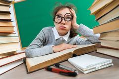 Exhausted or bored young student around a lots of books. Photo of student in classroom, education concept stock photography