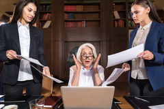 Exhausted boss and her female colleagues posing in an office Royalty Free Stock Images
