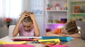 Exhausted boy and girl sitting at table, tired after drawing, falling asleep stock image