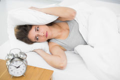 Exhausted brunette woman covering her ears with pillows Stock Photos