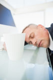 Exhausted businessman asleep at work. In front of his pc Royalty Free Stock Photography