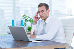 Exhausted businessman drowsing on his laptop Stock Photo