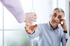 Exhausted businessman in his office. Exhausted businessman working in his office and having a headache, his assistant is handing him a glass of water, stress and Stock Image