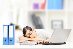 Exhausted businessman sleeping on a desk in his office stock photos