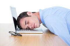 Exhausted businessman sleeping head on laptop Royalty Free Stock Images