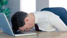 Exhausted businessman sleeping head on laptop Stock Photography