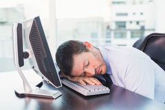 Exhausted businessman sleeping at his desk Royalty Free Stock Photography