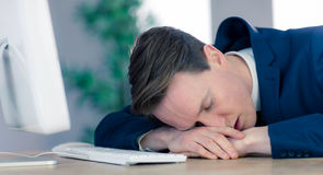 Exhausted businessman sleeping at his desk Royalty Free Stock Photos