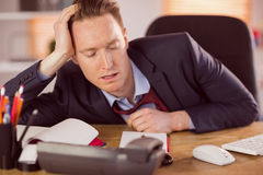 Exhausted businessman sleeping at his desk Stock Photography