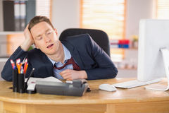 Exhausted businessman sleeping at his desk Stock Image