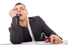 Exhausted businessman sleeping at his desk yawning Stock Photo
