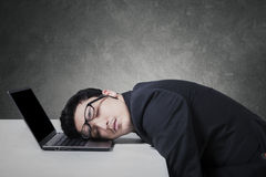 Exhausted businessman sleeping on his laptop Stock Images