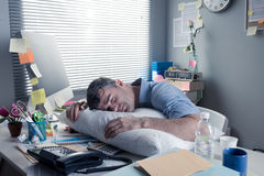 Exhausted businessman sleeping at workplace Stock Photography