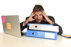 Exhausted businessman suffering stress at office computer desk holding paperwork folders. Tired and frustrated businessman desperate face expression suffering Stock Photo
